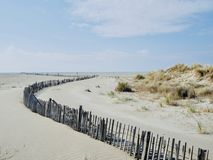 Sand dunes on the beach. A fence to protect the environment from flying sand at the beach of Mediterranean Sea Royalty Free Stock Photography