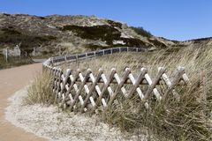 Fence through dunes royalty free stock photography