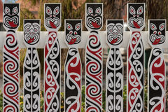 Fence with traditional Maori faces Stock Image
