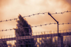 Fence with two rows of barbed wire. Dramatic atmosphere - a fence with two rows of barbed wire - a symbol of lack of freedom, prohibition, taboo Stock Photos