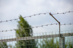 Fence with two rows of barbed wire. A symbol of lack of freedom, prohibition, taboo Royalty Free Stock Image