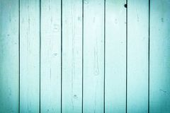 A fence of vertical light turquoise boards. Blank background with a texture of wooden slats. Photo with a vignette royalty free stock image
