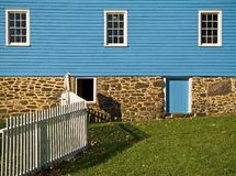 Fence and Wall. A composition of a bright blue historic mill and a white picket fence in Freehold New Jersey Stock Image