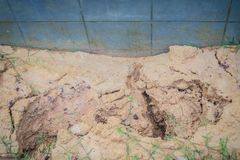 Fence wall of the newly built housing is tilted and collapsed du. E to high earthwork and heavy rainfall, causing the soil in the house to weaken and flow out Royalty Free Stock Photo