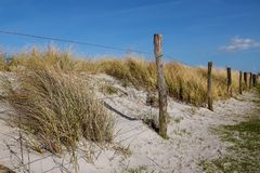 Fence with weathered wooden stakes in front of the sand dunes on. The beach of the Baltic Sea, blue sky, copy space, selected focus, narrow depth of field royalty free stock images