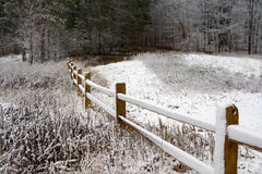 Fence in Winter Snow. A split rail fence in winter that is covered with snow in a heavily wooded section of Michigan Royalty Free Stock Images