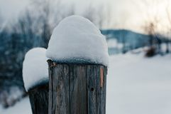 Snow-capped fence wooden beam royalty free stock image