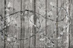 Fence wooden with the peeled-off paint and with a barbed wire. Fence wooden gray with the peeled-off white paint and with a barbed wire royalty free stock image