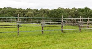 Fence of wooden poles. And beams to limit the movement of livestock, summer royalty free stock images
