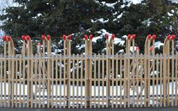 A fence of wooden sledges with a cristmas tree in the background. Snow on the cristmas tree stock photos