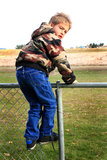 On the Fence. A young 6 year old fearlessly climbing on a fence wearing a warm coat Royalty Free Stock Photo