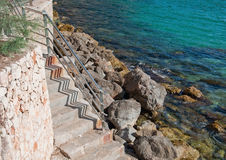 Fence and zigzag. Coastal landscape with metal fence and zigzag shadow on staircase near green ocean on a sunny summer day in Mallorca, Balearic islands, Spain Royalty Free Stock Photography