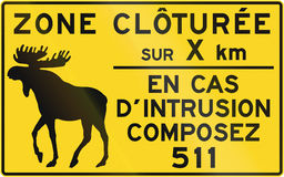 Fenced Area in Canada. Road sign in Quebec, Canada. The text means: Fenced area for XX km - In case of intrusion call 511 Royalty Free Stock Photography