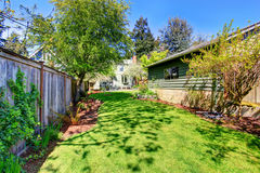 Fenced back yard with child's swing and green shed. Stock Image
