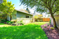 Fenced back yard with child's swing sit and green shed behind. Royalty Free Stock Images