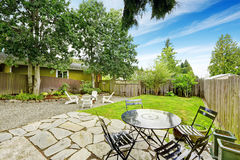 Fenced back yard with patio area and white adirondack chairs. Royalty Free Stock Photo