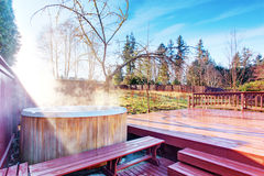 Fenced backyard area with hot tub and walkout deck. Fenced backyard area with hot tub and wooden walkout deck stock photo