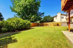 Fenced backyard with green lawn and bushes. Royalty Free Stock Image