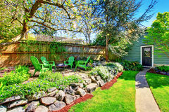 Fenced backyard with green lawn and patio area. View of the blue shed. Stock Image