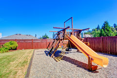Fenced backyard with playground for kids Royalty Free Stock Photo