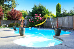 Fenced backyard with small beautiful swimming pool Royalty Free Stock Photos