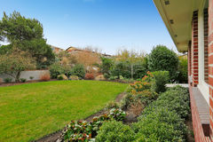 Fenced backyard. View of lawn and flower beds Stock Photos