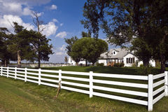 Fenced Farmhouse and Barn. White rail fence surrounds tidy farmhouse in Kansas royalty free stock photo