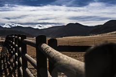 Fenced In. Fence running along the outside of a ranch with the mountains of beautiful Colorado in the distance Royalty Free Stock Photography