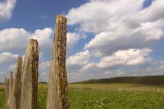 Fenced field against during the white beauty clouds royalty free stock photo