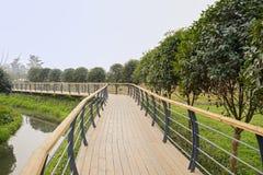 Fenced footbridge near stream in sunny spring Stock Image