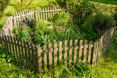 Fenced idyllic small flower garden Stock Photos