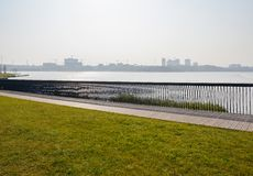 Fenced lawn and planked path along lakeside in sunny winter afternoon. Fenced planked path and grassy lawn along the lakeside in sunny winter afternoon,Tianfu stock photos