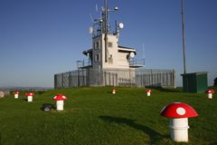 Fenced off signal house with tall antenna mast for shipping navigation on Mount Victoria, Devonport, Auckland, New Zealand. Radio building with long pole for stock photos