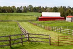 Fenced Pastures With Barn. Fenced green pastures with a red barn in a rural landscape setting surround by trees Stock Photo
