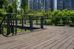 Fenced and planked footbridge in verdant summer at modern city Stock Image