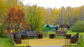 Fenced recreation area against children playground in park. Empty fenced recreation area with wooden benches against children playground and autumn trees in stock footage
