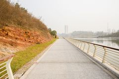 Fenced riverside path at hill foot in sunny winter afternoon. Fenced riverside path at the hill foot in sunny winter afternoon,Chengdu,China stock photography