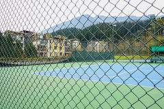 Fenced tennis court before houses in mountains Royalty Free Stock Photo