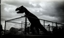 Fenced Tyrannosaurus sculpture. Black and white silhouette image of a Tyrannosaurus dinosaur sculpture taken in Manitowoc, Wisconsin with vintage camera on film Stock Images