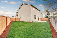 Fenced and unfurnished back yard with grass. Royalty Free Stock Photography