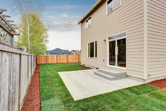 Fenced and unfurnished back yard with grass. Stock Photos