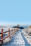 Fenced walk to ballybunion castle in snow. Snow covered view of atlantic ocean and castle in ballybunion on a frosty snow covered winters day Royalty Free Stock Photos