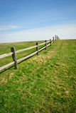 Fenceline on green grass rise Royalty Free Stock Photos