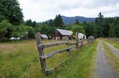 Fenceline a lo largo de una calzada que lleva a una granja del valle fotos de archivo