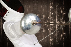 Fencer athlete. With sword and mask in action royalty free stock image