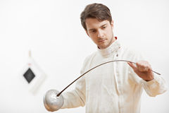 Fencer checking rapier foil. Young fencer in protective sport wear inspecting rapier foil stock photography