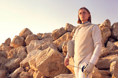 Fencer man holding fencing mask and a sword looking forward on rocky mountains landscape stock photography