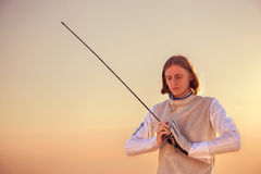 Fencer man holding his sword in both hands looking down on sunset background Royalty Free Stock Image