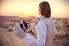 Fencer man holding his sword on the shoulders on a rocky background and looking forward to the sun goes down. Back view close-up of a fencer man wearing white Stock Photos