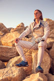 Fencer man holding sword and sitting on top of rock on a blue sky background and looking forward royalty free stock image